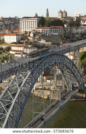 Dom Luis I Bridge. Built in 1887, the Dom Luis I Bridge is a two tiered bridge that spans the fast flowing Douro River that runs through Porto, Portugal. The river cuts a deep valley through Porto. - stock photo