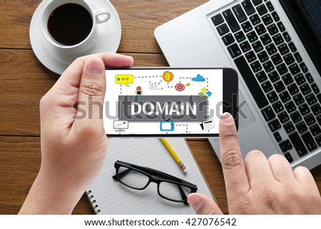 DOMAIN message on hand holding to touch a phone, top view, table computer coffee and book - stock photo