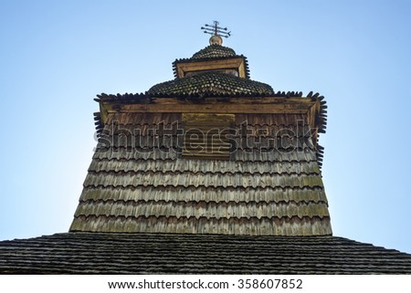 Dome and cross of the ancient wooden church (XVIII century) in the village Huklyvy in the Ukrainian Carpathians. - stock photo