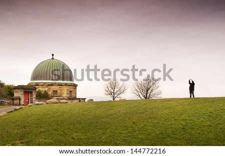 Dome building in Calton Hill, Edinburgh. There are two leafless trees and one person, the sky is overcast. - stock photo