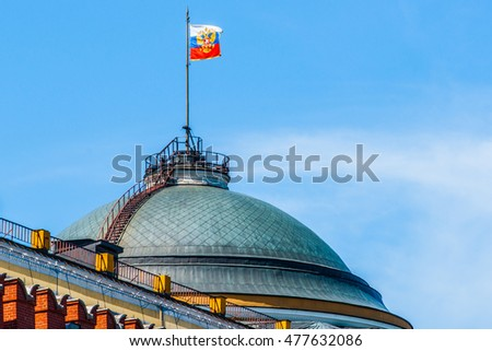 Dome of the Senate building of Moscow Kremlin and the three color flag - the President of the Russian Federation Standard against blue sky and white clouds