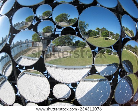 domed mirror with reflection of city and gardens - stock photo