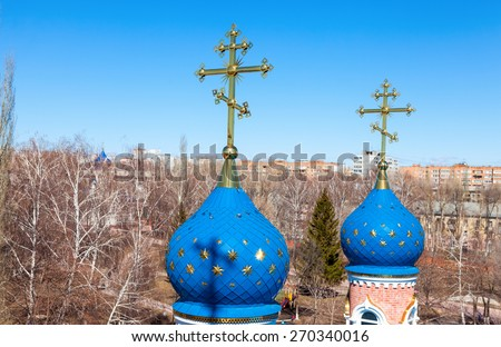 Domes of Russian orthodox church with cross against blue sky - stock photo