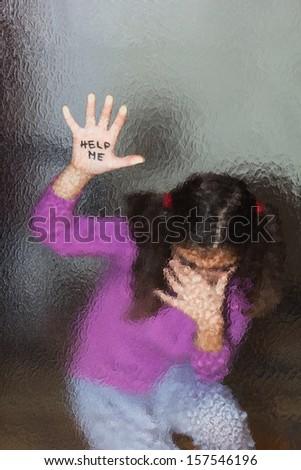 Domestic and family violence. Little girl asking for help. Look through the glass. - stock photo