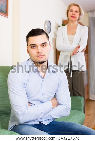 Domestic conflict between adult son and senior mature mother  - stock photo