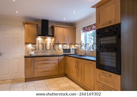 Domestic Kitchen / Modern domestic kitchen with a light oak shaker style design and tiled floor and backsplash - stock photo