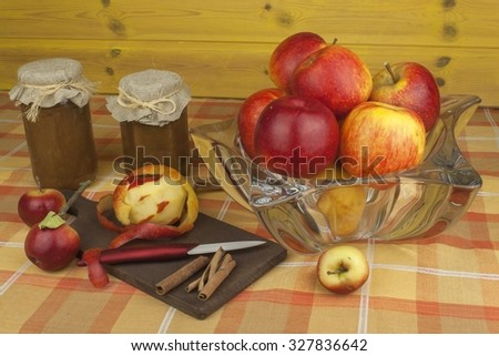 Domestic production of apple marmalade and cinnamon. Apple jam on the kitchen table. Processing autumn harvest of apples. - stock photo
