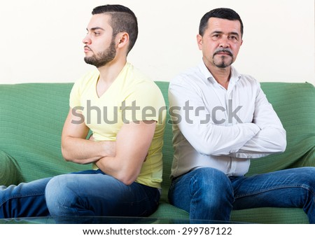 Domestic quarrel between father and adult son at the sofa in the living room - stock photo