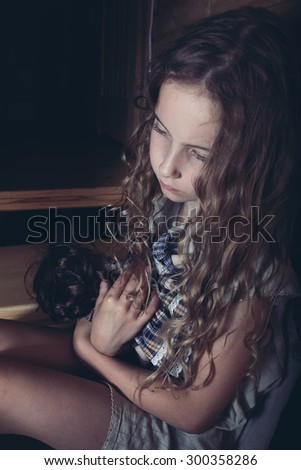 Domestic violence - a girl hugging a doll - stock photo