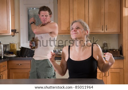 Domestic violence - angry beer-drinking man threatens woman (with bruises) - stock photo