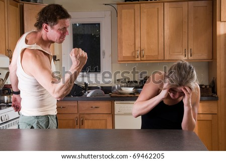 domestic violence - man with clenched fist threatens woman - stock photo