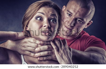 Domestic violence woman being abused and strangled by strong man - stock photo