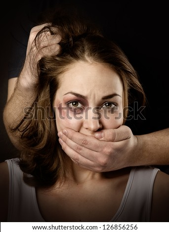 Domestic violence woman being abused and strangled by strong man. on dark background - stock photo