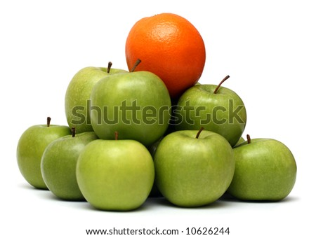 domination concepts - orange on pyramid of green apples - stock photo