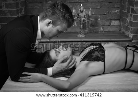 Domineering lover kisses his sexy submissive in loft interior - stock photo