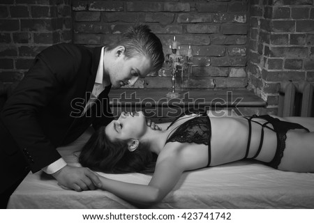 Domineering lover kisses his sexy submissive in loft interior