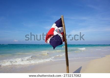 Dominica Republic flag swinging beside the Caribbean beach - stock photo
