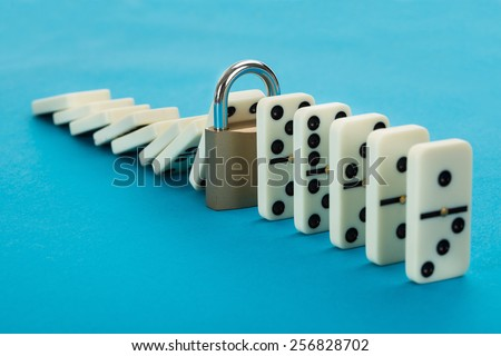 Domino And Lock In A Row Over Blue Background - stock photo