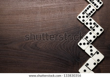 domino pieces forming zigzag on wooden table - stock photo