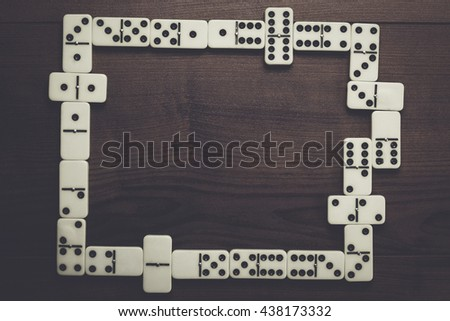 domino pieces on dark brown wooden background - stock photo