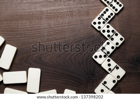domino pieces on the dark brown wooden table background - stock photo
