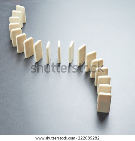 Domino's effect composition of a multiple domino bones placed in a row over the dark gray surface
