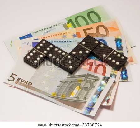 Domino standing on euro currency. - stock photo