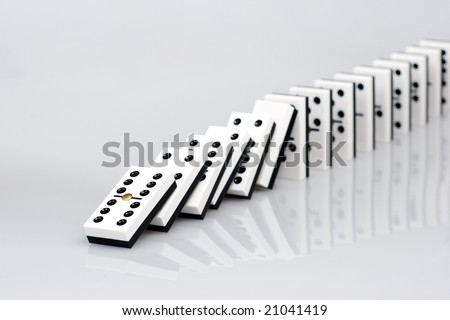 Dominos falling down in chain reaction - stock photo