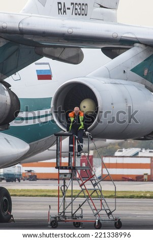 DOMODEDOVO AIRPORT (DME), RUSSIA, SEPTEMBER 26, 2014: Service man work with engine of IL-76TD Alrosa airlines arrived in Domodedovo Airport September 26, 2014 in Moscow region, Russia - stock photo