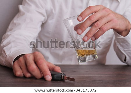Don't drink and drive concept. Close up of man hand drinking beer and holding car keys. Responsibly and safety driving  - stock photo