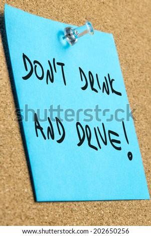 Don't drink and drive sign written on blue post it paper pinned to a cork bulletin board. - stock photo