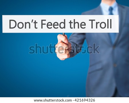 Don't Feed the Troll - Businessman hand holding sign. Business, technology, internet concept. Stock Photo - stock photo