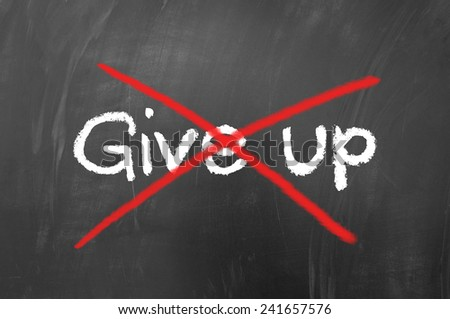 Don't give up concept written on school blackboard - stock photo