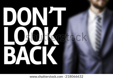 Don't Look Back written on a board with a business man on background - stock photo