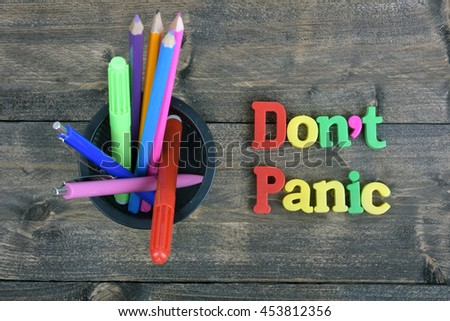 Don't panic word on wooden table - stock photo