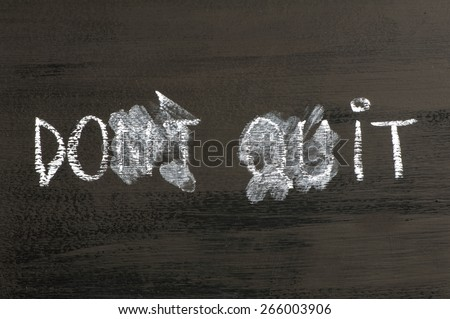 Don't Quit transformed in Do It  message isolated on black background. Chalk drawing on blackboard. Business Concept image. - stock photo