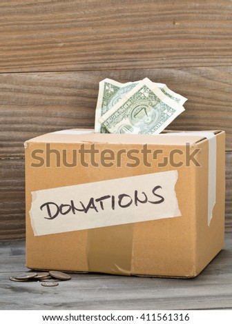 Donation carton box with dollar bills and coins on wooden table background - stock photo