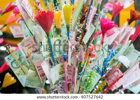 Donation Merit Money Tree in Thai Temple. Money tree at Buddhist temple in Thailand consisting of banknotes donated by visitors for maintenance of the temple. Close up and select focus, close up image - stock photo