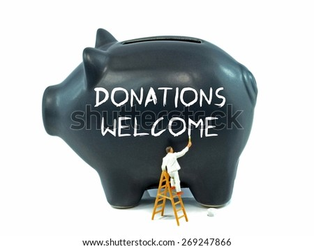 Donations Welcome message painted on a piggy bank, soft focus - stock photo