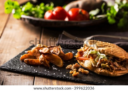 Doner kebab with fried potato on served wooden table - stock photo
