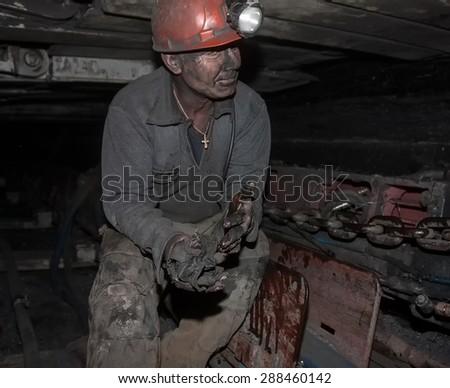 Donetsk, Ukraine - August, 16, 2013: Miner repairs coal mining combine. Mine name Chelyuskintsev - stock photo