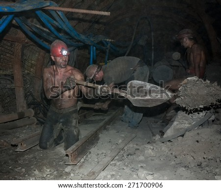 Donetsk, Ukraine - August, 16, 2013: Miners perform heavy manual labor in low light conditions and dusty. Mine is named Chelyuskintsev - stock photo