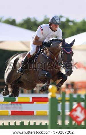 "DONETSK, UKRAINE - JULE 12, 2009: Oleg Krasyuk overcomes the obstacle at the racehorse in the jumping competition ""Donbass Tour 2009"" CSN** 3 stage on Jule 12, 2009 in Donetsk, Ukraine."