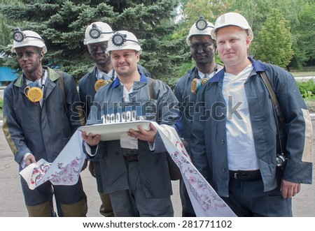 Donetsk, Ukraine - 26 July, 2013: Miners with coal symbolic ingot at the ceremony in honor of 1000000 tons of coal mined in Donetsk coal and energy company in the current year - stock photo