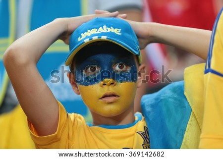 """DONETSK, UKRAINE - JUNE 15: Ukraine boy of national football team supporters show their support during UEFA EURO 2012 on """"DONBAS ARENA"""" soccer stadium in Donetsk on June 15, 2012 in Donetsk, Ukraine. - stock photo"""