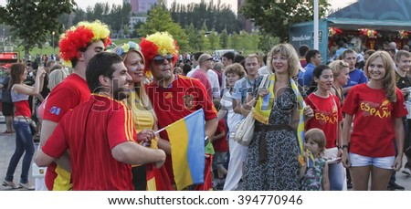 DONETSK, UKRAINE - JUNE 23, 2012: Unidentified Spanish soccer fans with Ukrainian girl before UEFA EURO 2012 match in Donetsk near Donbass Arena - stock photo