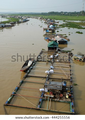 DONG NAI, VIET NAM- JUNE 5: Group of floating house on La Nga fishing village, river with green grass and hyacinth, residence of people who live with fish farming at Dongnai, Vietnam