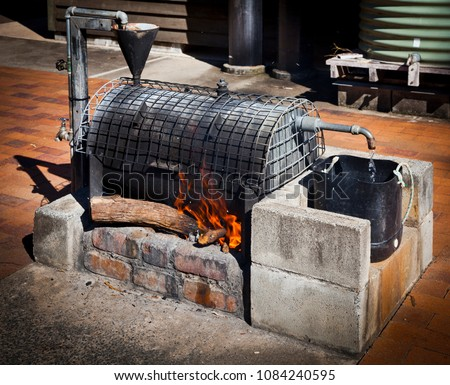 Donkey Boiler, Wood fired water boiler, Flames from burning wood lick an iron boiler while water flows out to a bucket.