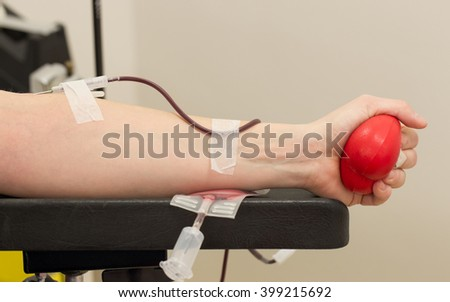 Donor in an armchair donates blood at hemotransfusion station, close-up - stock photo