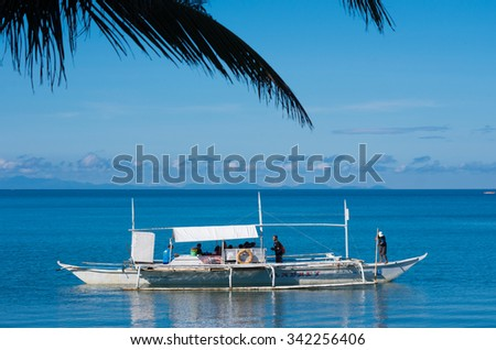 DONSOL, PHILIPPINES - JUNE 2, 2015: Traditional philippine bangkas with tourists on their way to see the whale sharks in the surrounding waters - stock photo